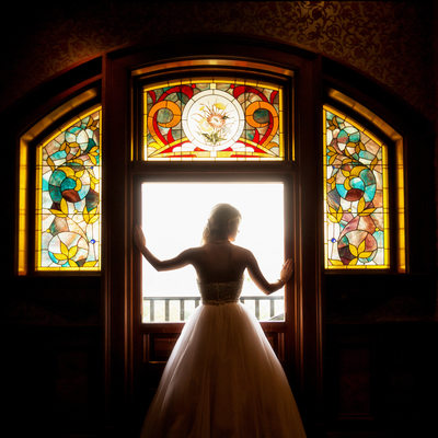 bride standing in front of stained glass window