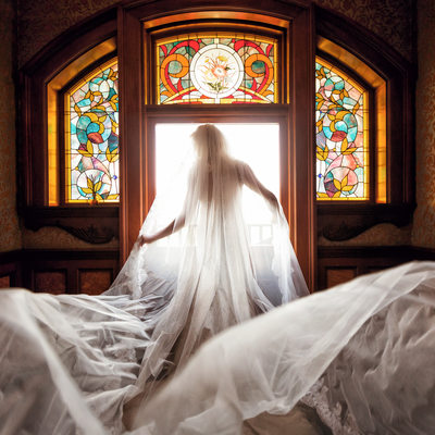 bride in front of Newhall mansion stained glass window