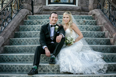 Bride and groom posing on newhall mansion stairs