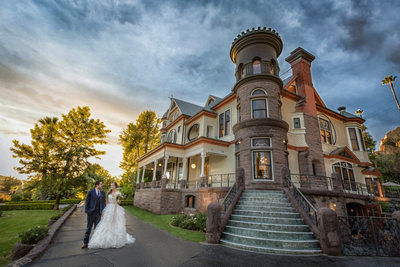 bride and groom in front of the newhall mansion