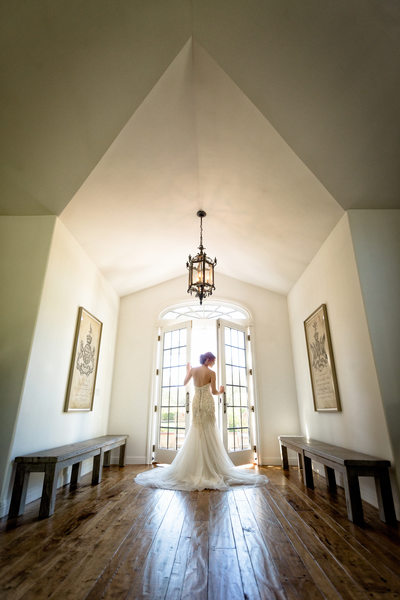villa aix vineyard bride standing in front of french doors under