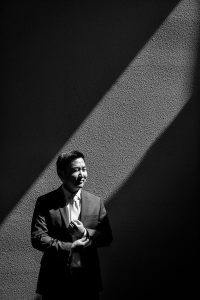black and white groom getting ready harsh light