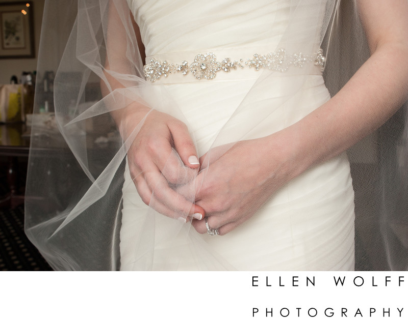 detail of the brides hands clasping her veil together