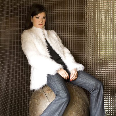 fur jacket photographed on a model sitting on a wooden ball