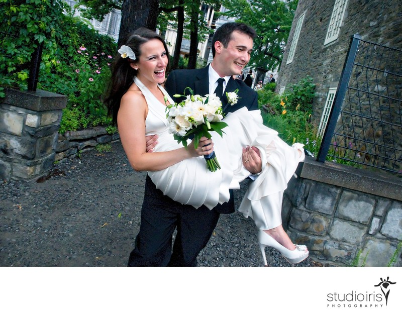 Groom running with bride in his arms after wedding ceremony at Chateau Ramezay in Montreal
