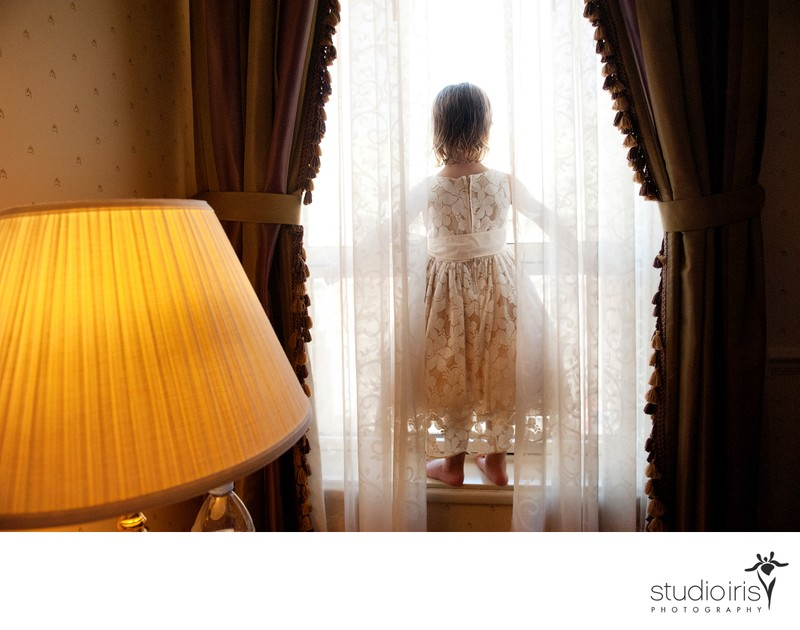 Little girl standing behind curtains on window ledge during Quebec City wedding