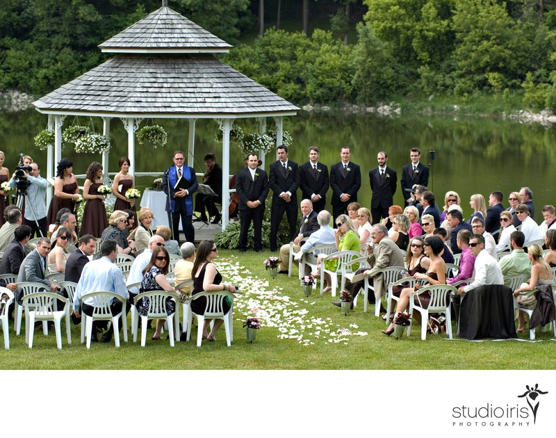 groom watching bride coming towards him at outdoor wedding ceremony a Au Vieux Moulin in Rigaud