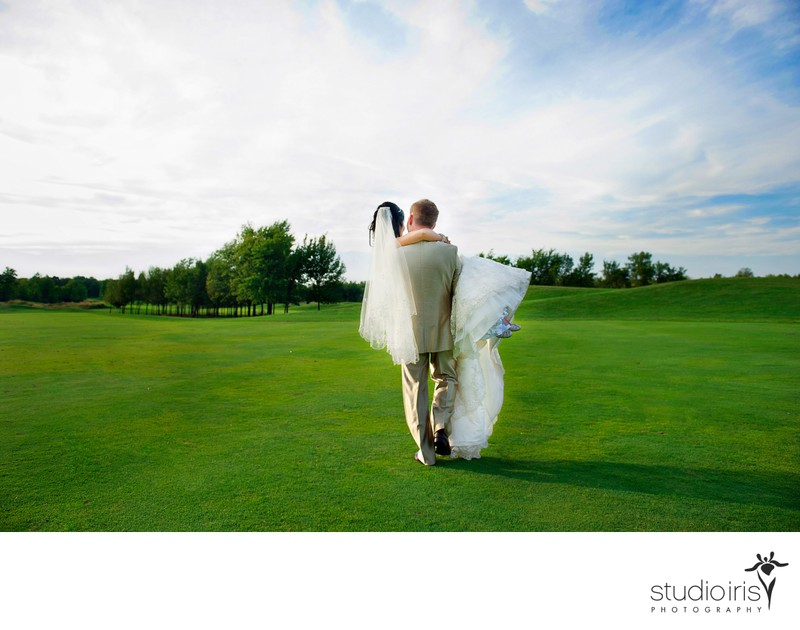 Groom carrying bride in his arms across the fairway at Golf St-Raphaël