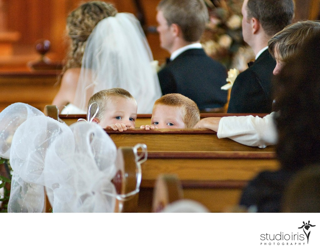 Two boys peeking mischievously over the pew during a wedding ceremony in Quebec's Eastern Townships