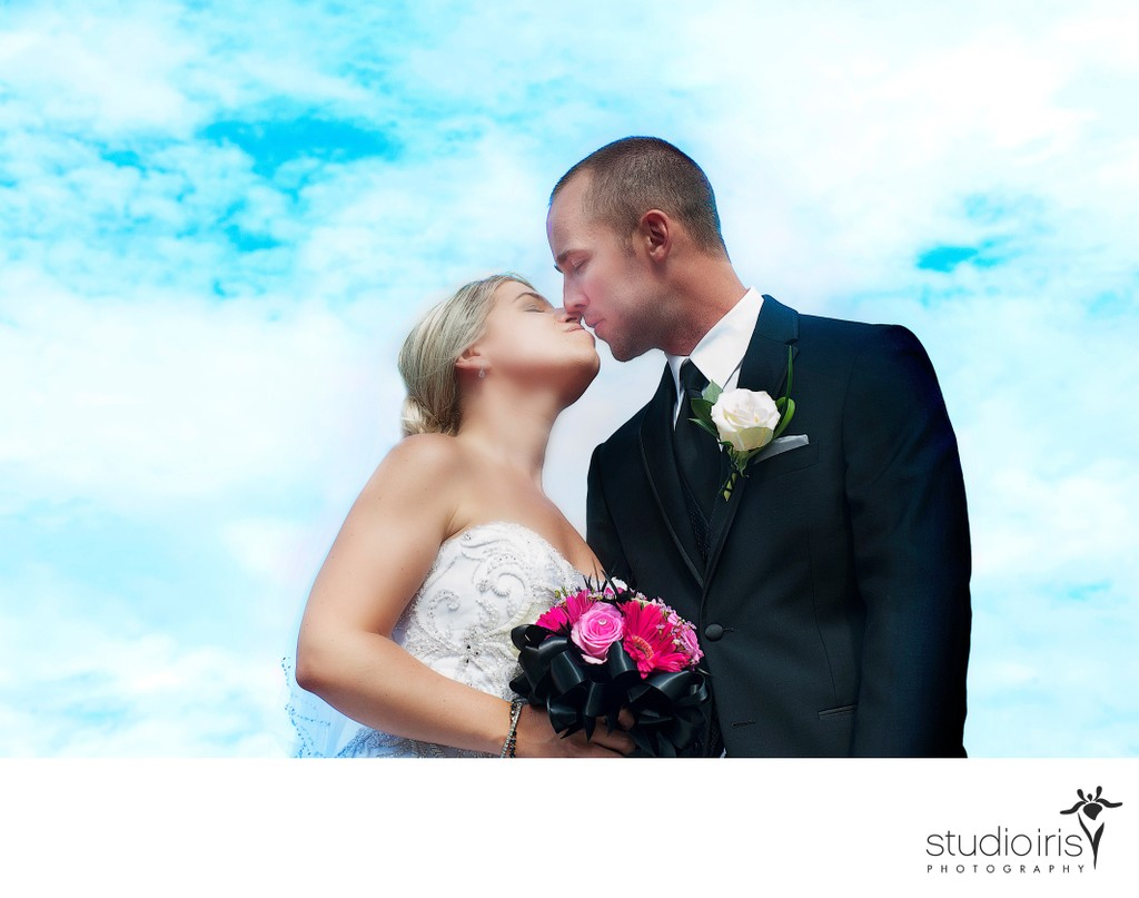 Bride and groom kissing against blue summer sky at montreal wedding