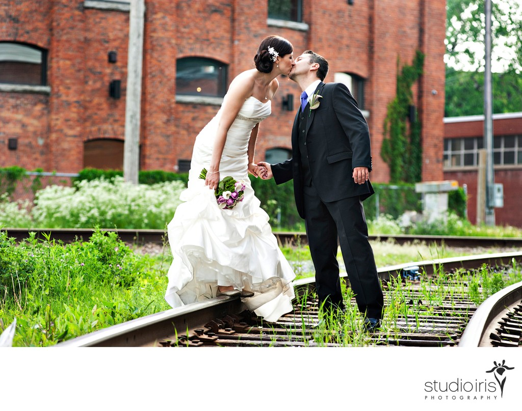 Bride and groom kissing on the railway tracks near Montreal's Atwater Market