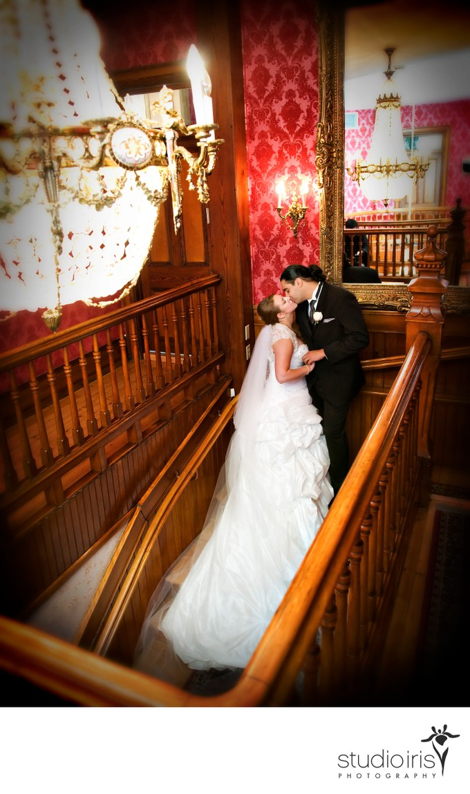 newlyweds kissing in the stairwell after their wedding at Chateau Saint Antoine