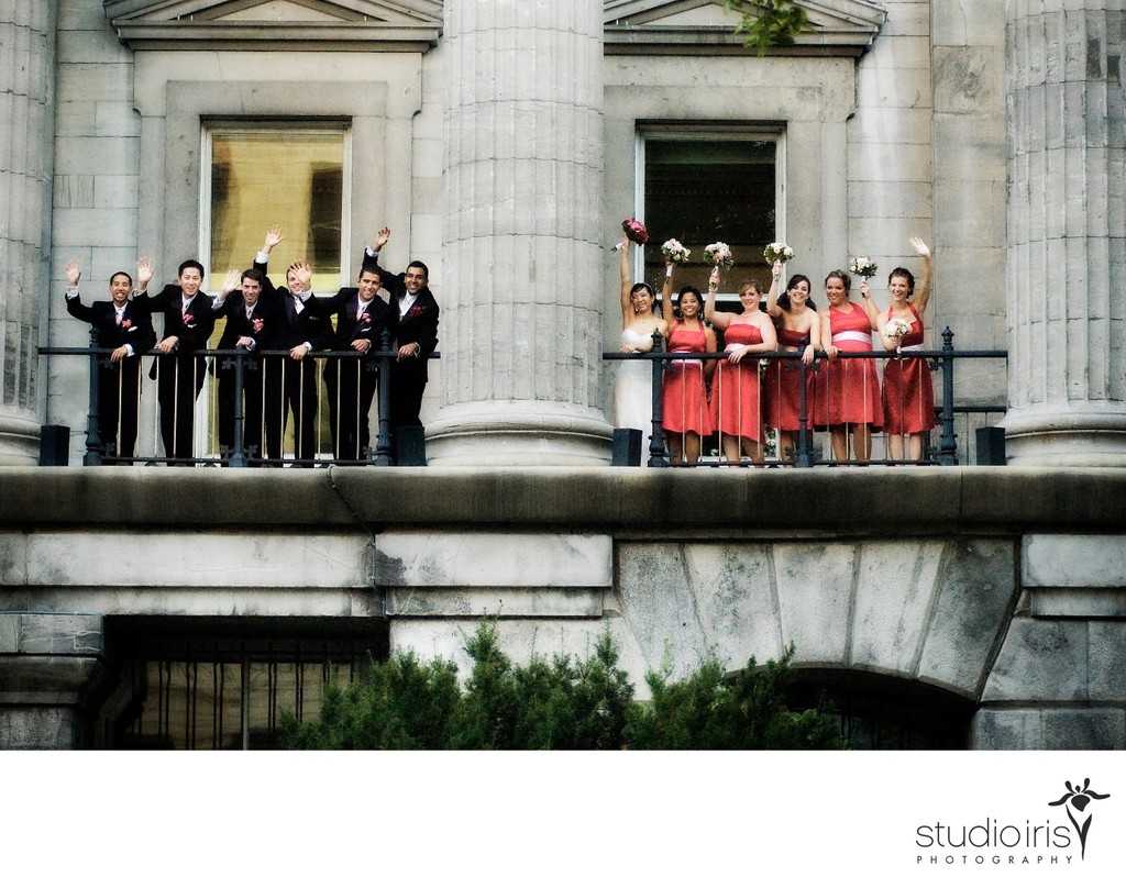 Bridal party waving from the balcony of a heritage building in Old Montreal