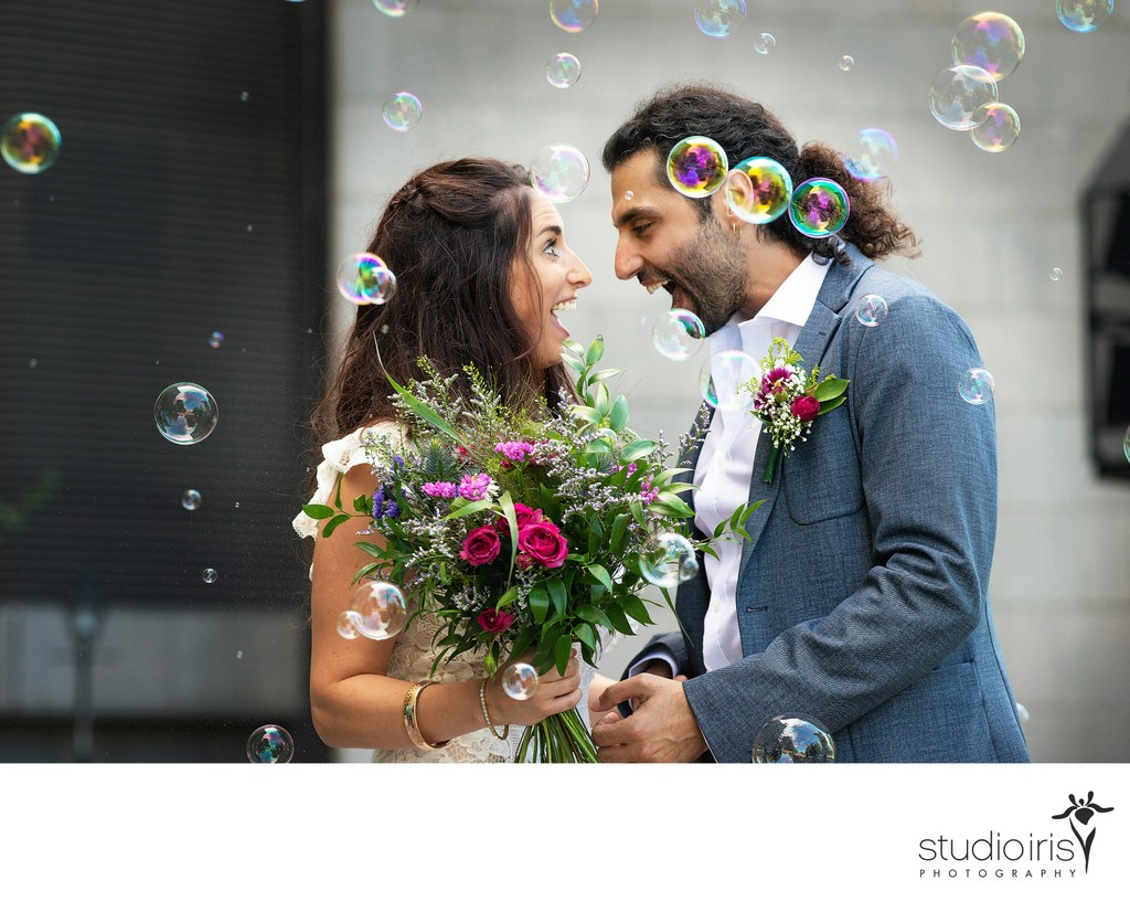Newlyweds in cloud of bubbles looking at each other in amazement  after their Montreal City Hall Wedding