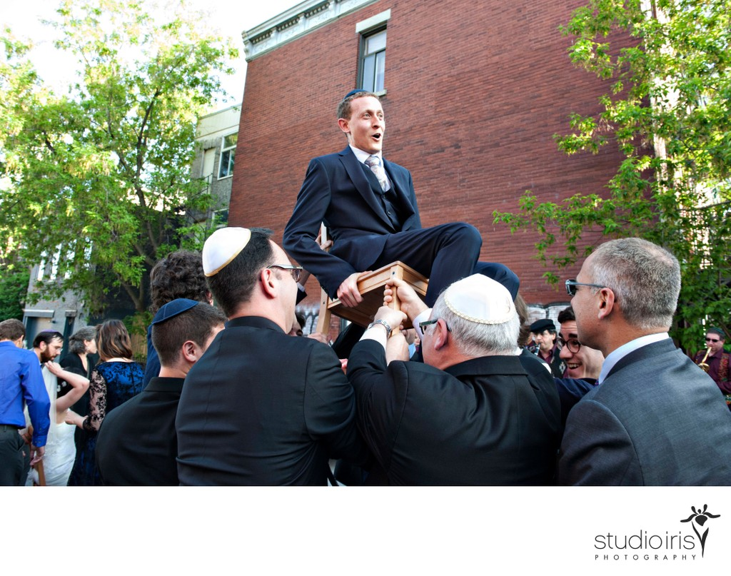 Groom on chair during hora dance outside Bagg Street synagogue in Montreal