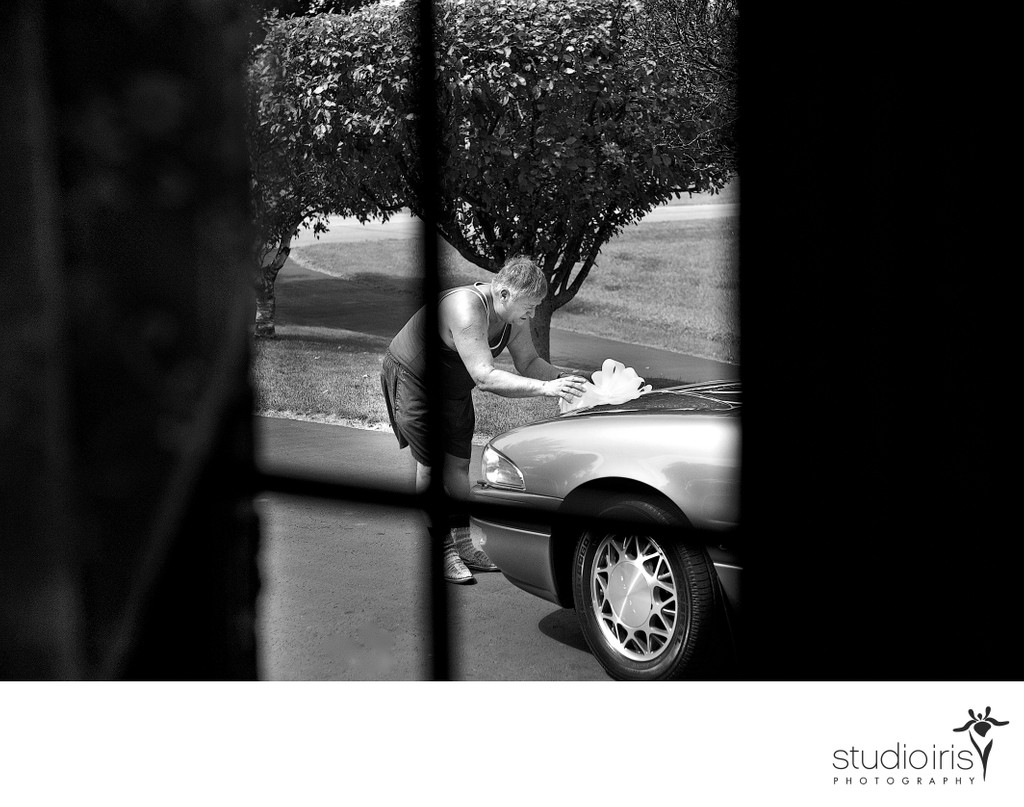 Father of the bride seen through window attaching wedding bow to car