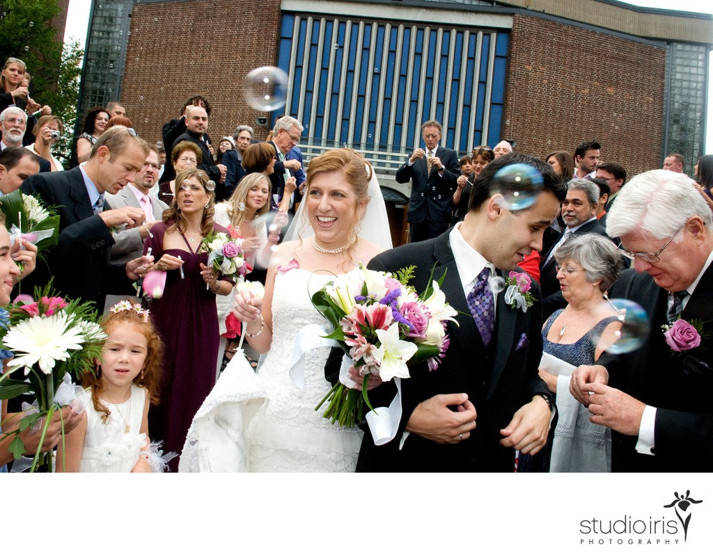 Bride and groom getting jostled in crowd as they leave St. George Cathedral after wedding
