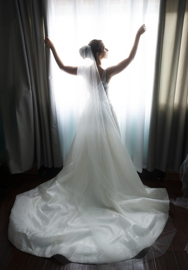 silhouette of bride in window on wedding dat