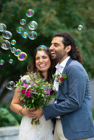 Bride and groom surrounded by bubbles after their civil mariage at Montreal's Hotel de VIlle