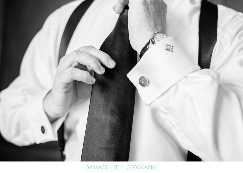 Groom Adjusting Tie With Monogrammed Cufflinks