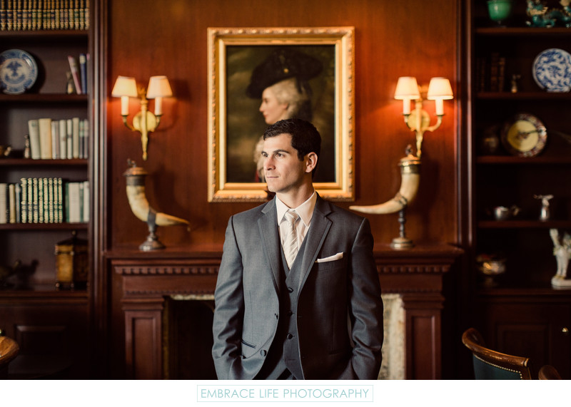 Handsome Groom Poses in Historic Themed Bar