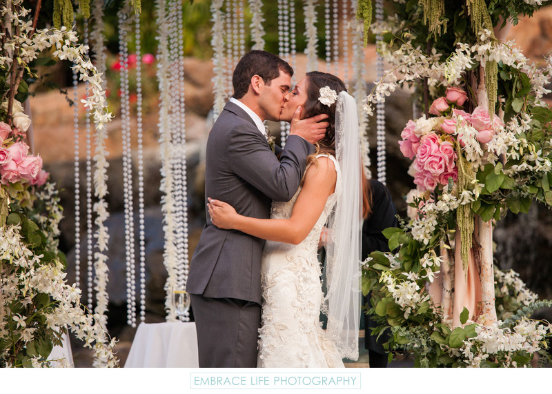 Husband and Wife Share First Kiss Under Floral Chuppah