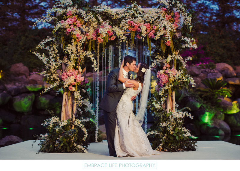 Beautiful Couple Kiss Under Garden Chuppah at Night