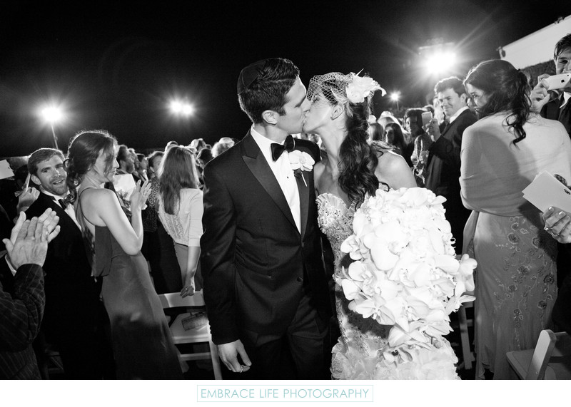 Bride and Groom Kiss During Ceremony Recessional