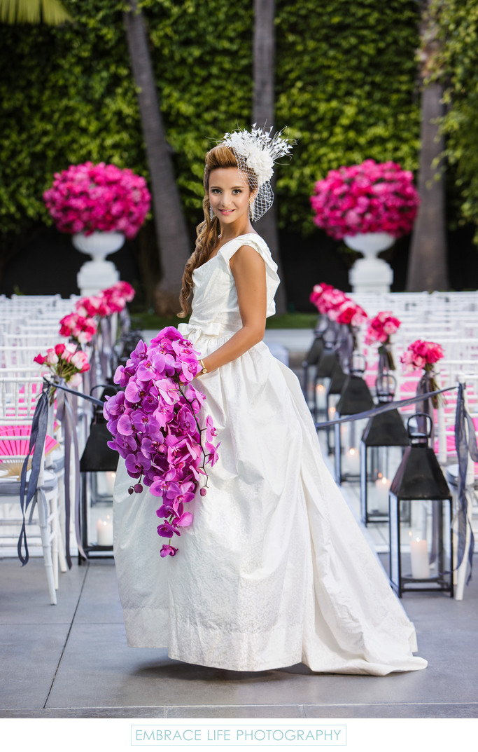 Bride Poses with Cascading Purple Orchid Bouquet
