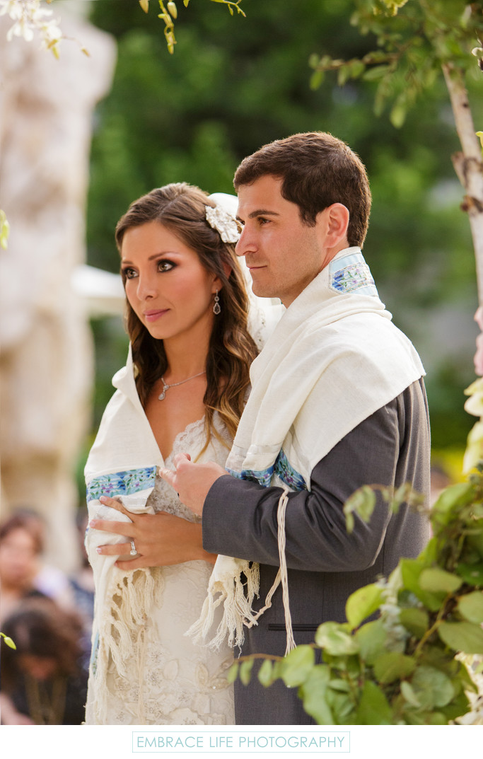 Bride and Groom Wrapped in Tallit Accept Rabbi Blessing