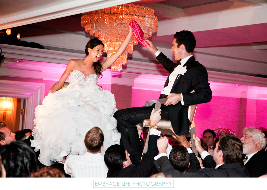 Bride & Groom in Chairs During Wedding Reception Hora