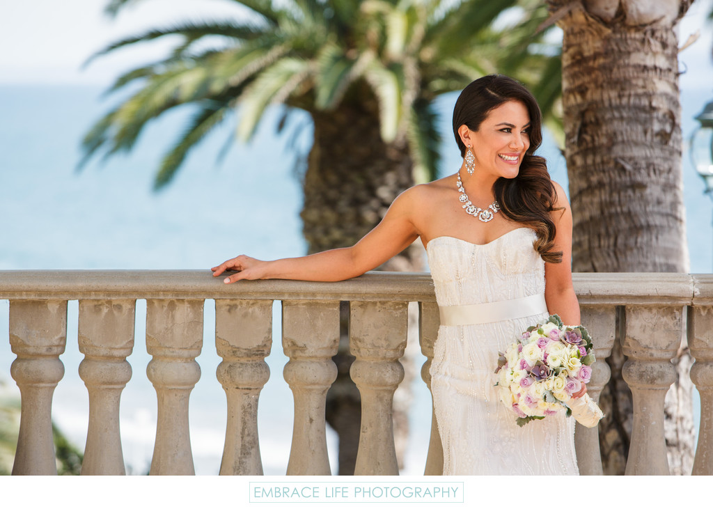 Bride Standing at Railing with Ocean View