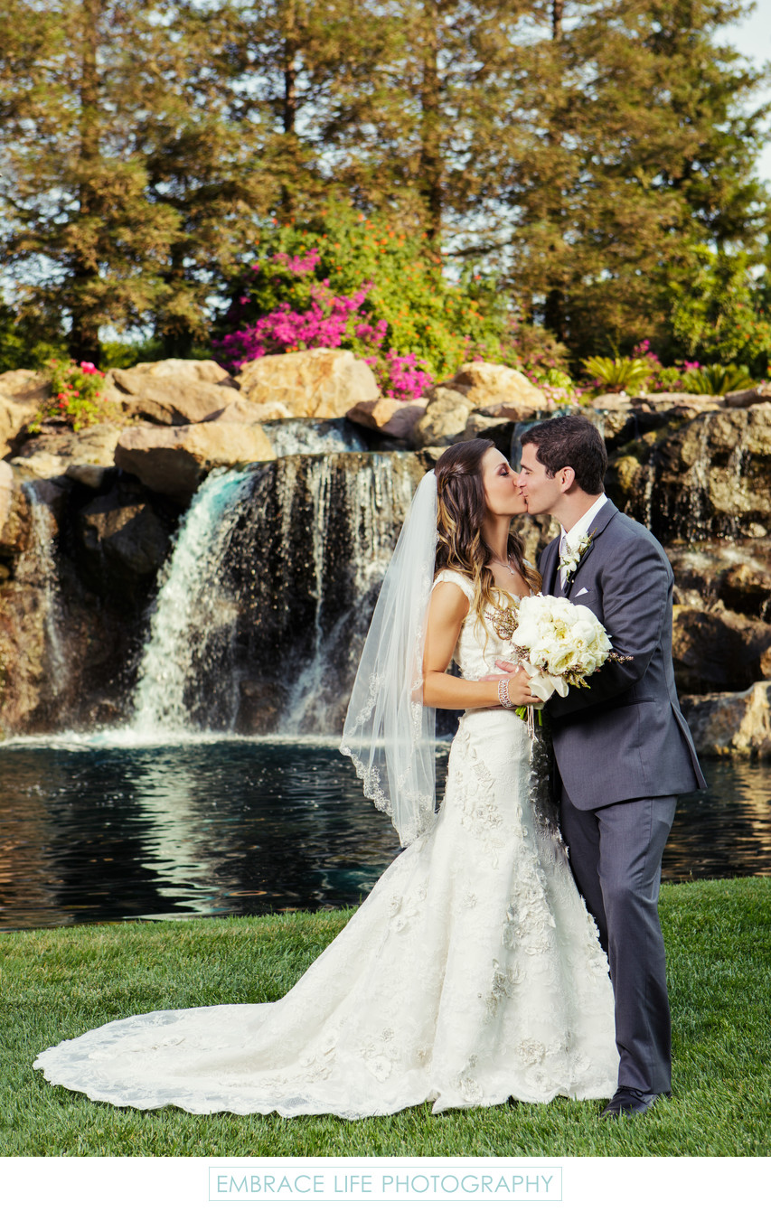 Husband and Wife kissing in Front of Waterfall