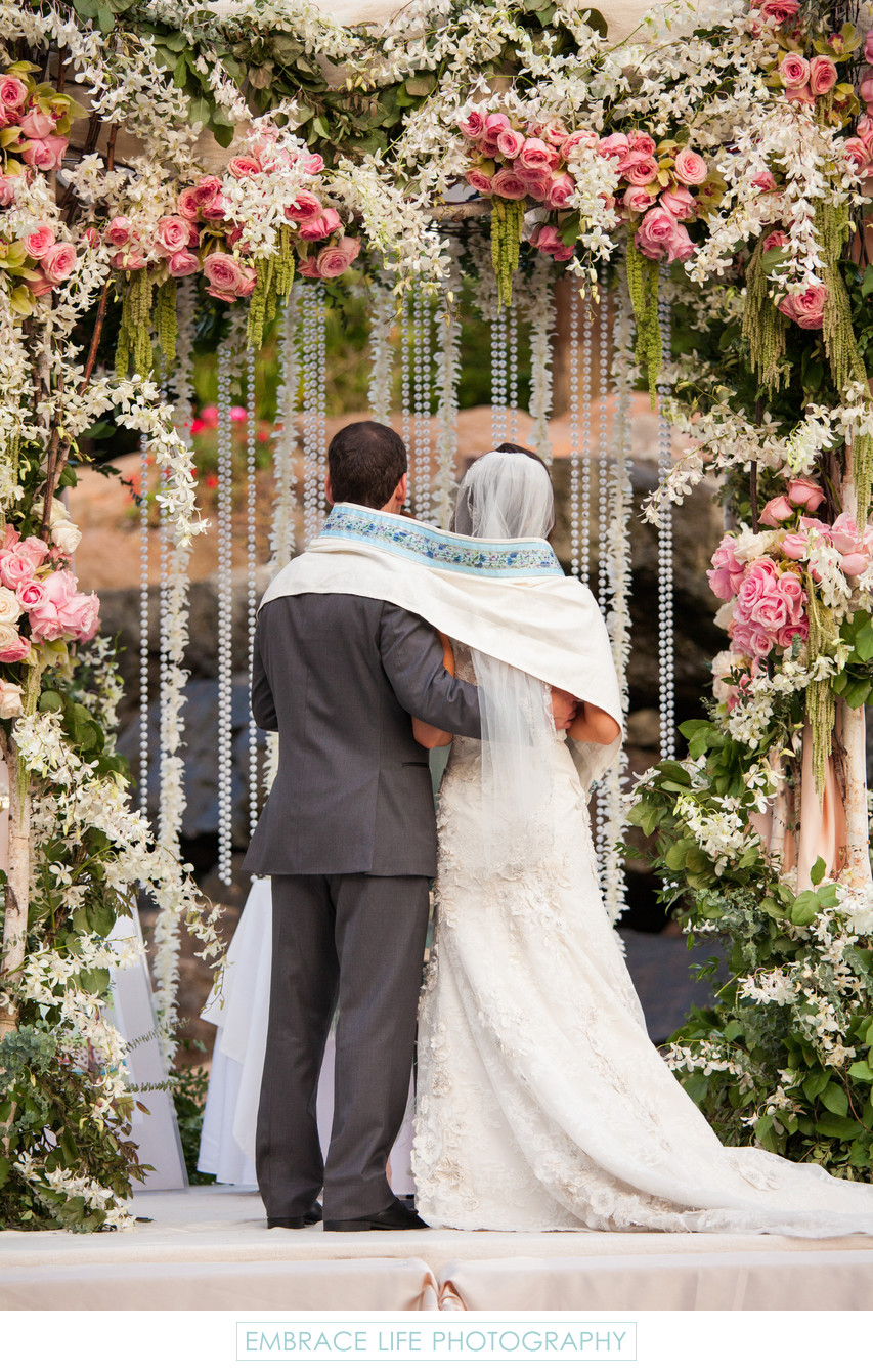 Bride and Groom Wrapped in Tallit Under the Chuppah