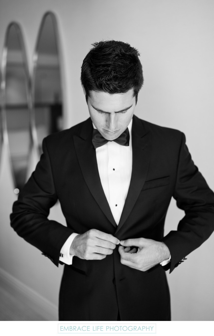 Groom in Black Bow Tie Buttons his Tuxedo Jacket