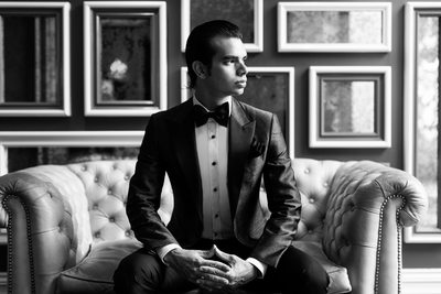 Black and White Photo of Groom Sitting on Tufted Sofa