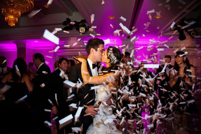 Bride & Groom Kiss Among Confetti at Wedding Reception