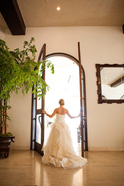 Bride Looking Out Tall Arched Doors
