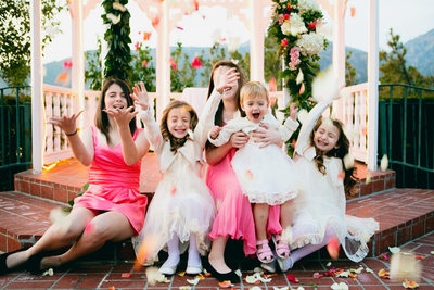 flower girls with rose petals in the air