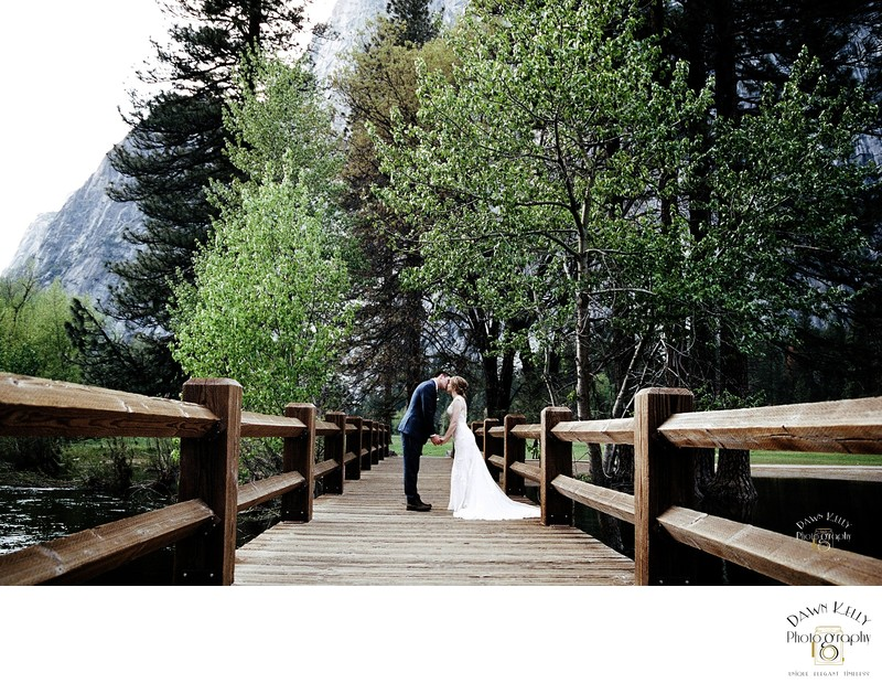 Bride and groom kiss at Swinging Bridge Yosemite