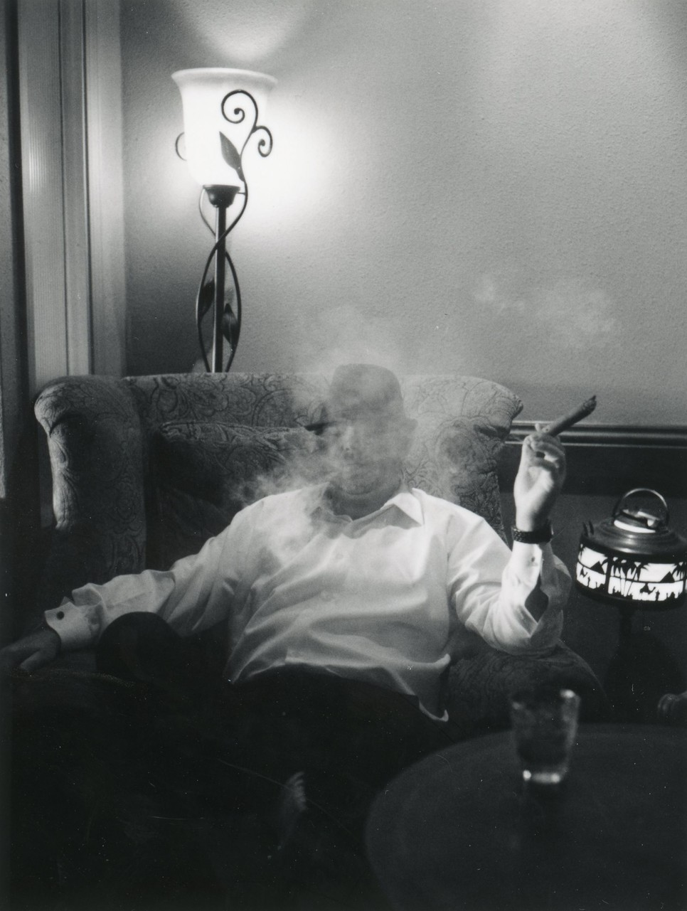 Black and white photo of groom smoking cigar