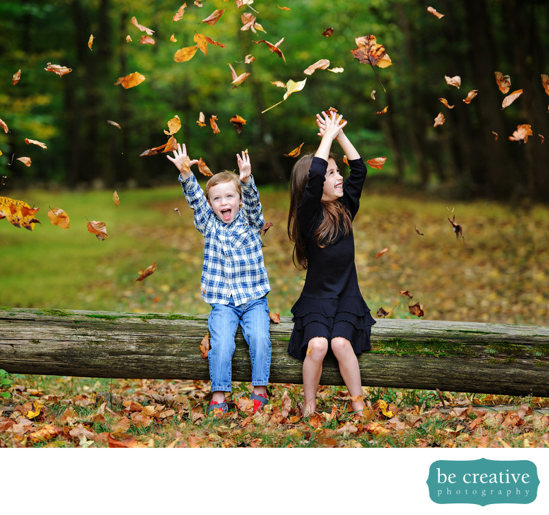 amazing fall portrait of children throwing leaves in nj