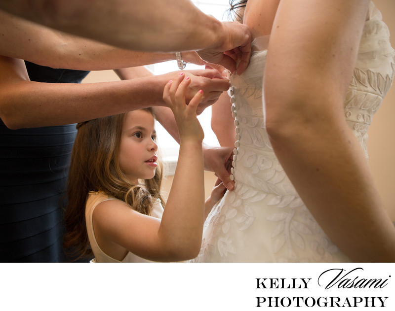 Flower girl helping bride prepare for wedding