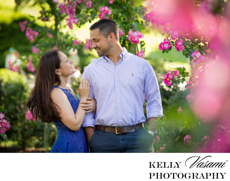 Couple surrounded by pink roses at engagement session