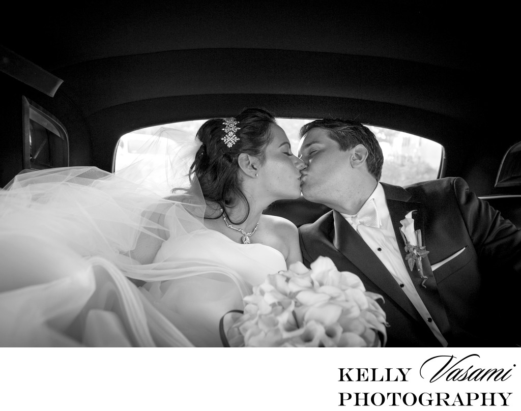 bride and groom kissing in classic limo