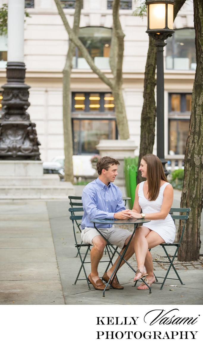 Engaged couple sits in bistro chairs outside of NYPL