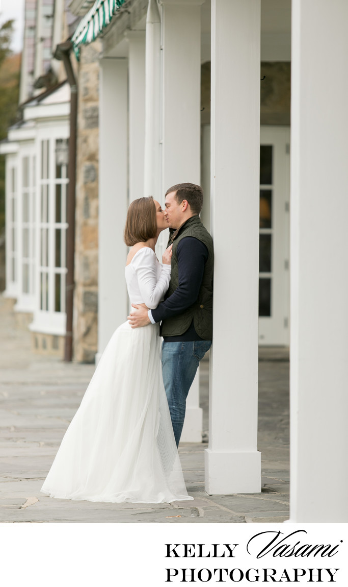 Columns & stone architecture surround an engaged couple
