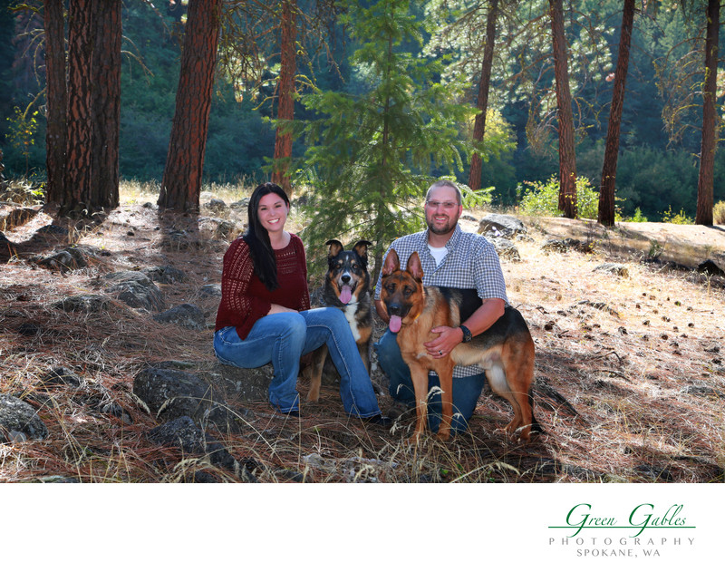 young couple with their two dogs in the woods