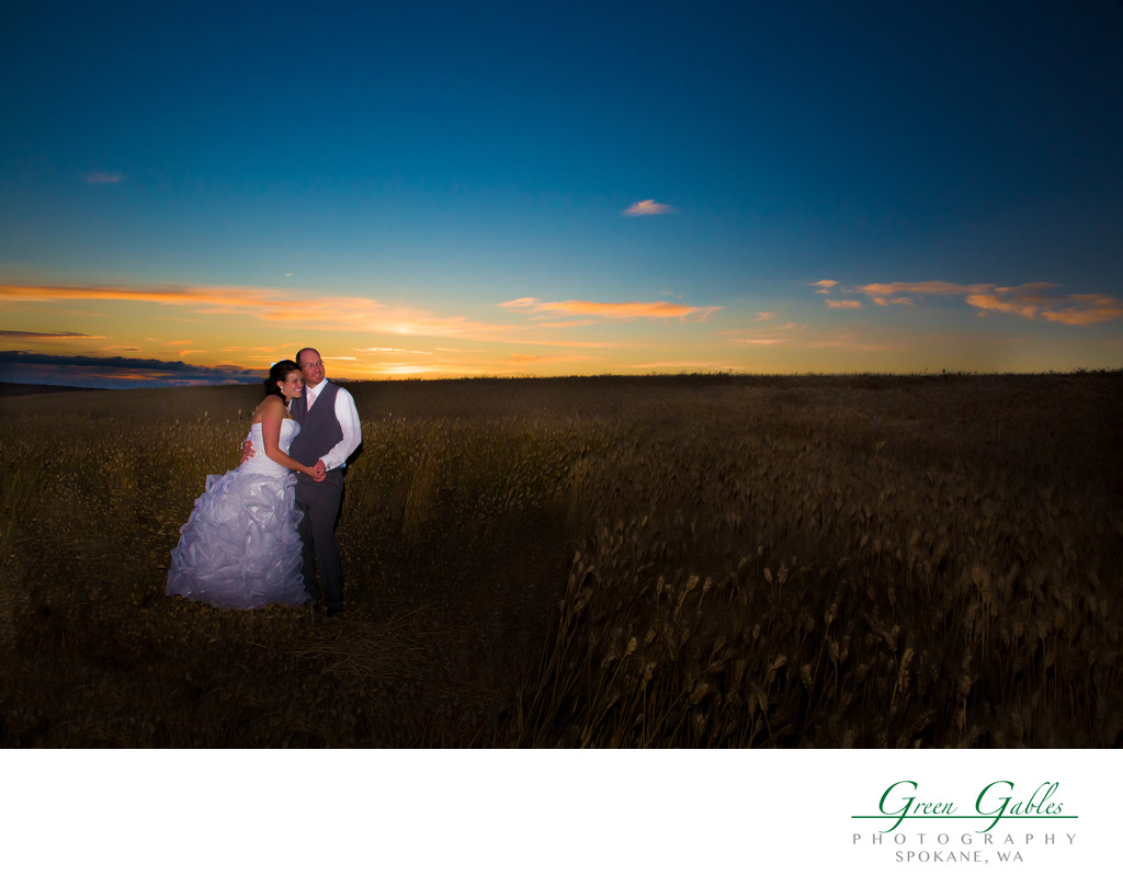 bride and groom in wheat field during sunset