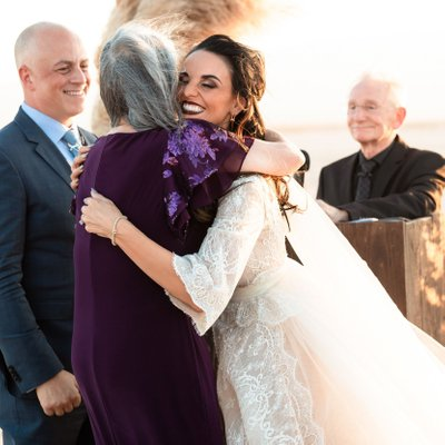 Bride hugs mother in law at ceremony